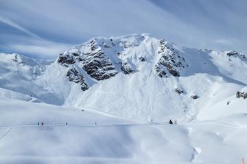 Verschneiter Berg mit Skifahrern