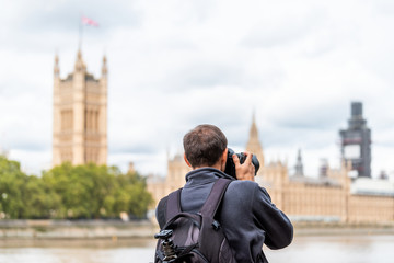 London, UK man photographer with backpack, tripod photographing, taking photo, picture of cityscape skyline of city with Thames River, Westminster during cloudy autumn on Albert Embankment