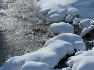 Schneebedeckte Steine im Bachbett