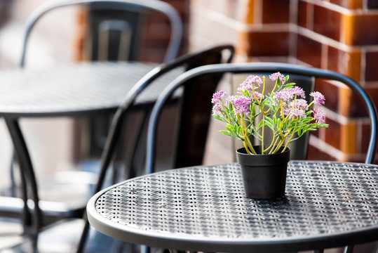 Closeup of empty table outside restaurant cafe metal chair on sidewalk street, purple flowers, flowerpot potted setting, nobody