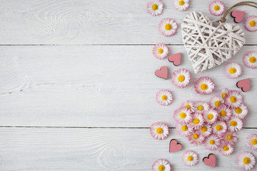 Daisies, petals and hearts on a wooden light background