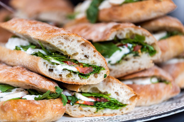 Spoed Fotobehang Snack Closeup of fresh display of stacked pile of panini bread, mozzarella melted cheese, vegetarian italian tomatoes, basil lettuce in store, shop, cafe buffet catering sandwiches