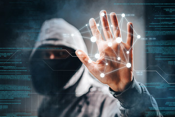 Cyber crime. Male hacker accessing to personal information. Hooded man with obscured face touching digital panel with mixed media and binary code. Virtual crime, cybersecurity concept.