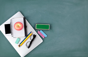 Back to school concept with technology and stationery on a green chalkboard background