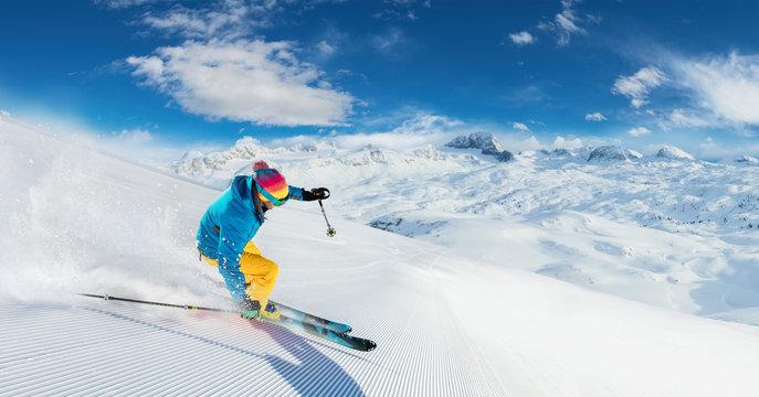 Alpine skier skiing downhill, panoramic format