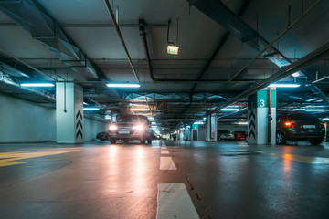 Illuminated underground car parking interior under modern mall with lots of vehicles and arrows on floor