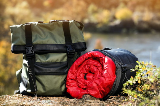 Backpack and sleeping bag on ground outdoors. Camping equipment
