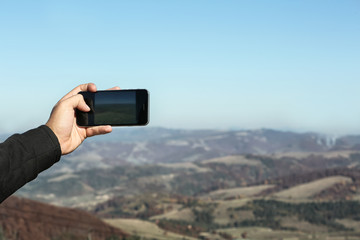Man taking photo of beautiful mountain landscape with smartphone