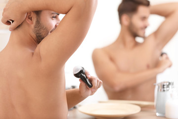 Handsome young man applying deodorant in bathroom. Space for text
