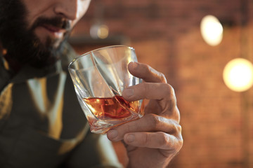 Man with glass of whiskey indoors, closeup