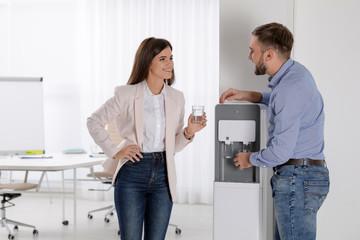 Employees having break near water cooler in office
