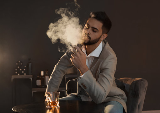 Man with glass of whiskey and cigar sitting at table indoors