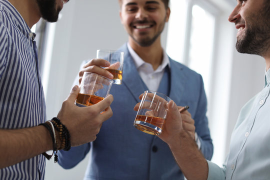 Group of friends drinking whiskey together indoors