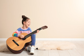Cute little girl playing guitar on floor in room. Space for text