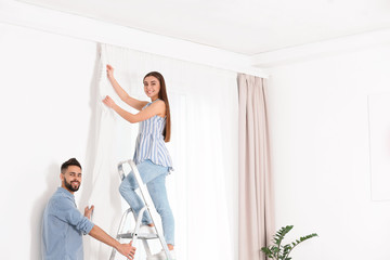 Young couple hanging window curtain in room. Space for text