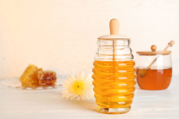 Glass jar with sweet honey on table against light background. Space for text