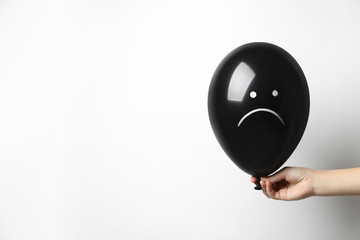 Woman holding balloon with sad face on white background, space for text. Threat of depression