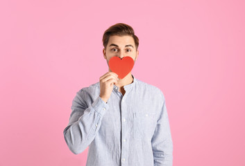 Portrait of young man with paper heart on color background