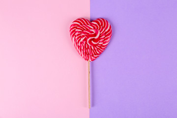 Heart shaped lollipop on color background, top view. Sweet love