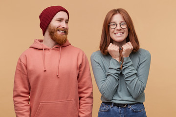 Indoor shot of handsome ginger beard male, looks at his girlfriend and smiles. Cheerful ginger female, smiles broadly, feels happy, keeps her eyes closed and hands near chin and dreams about win