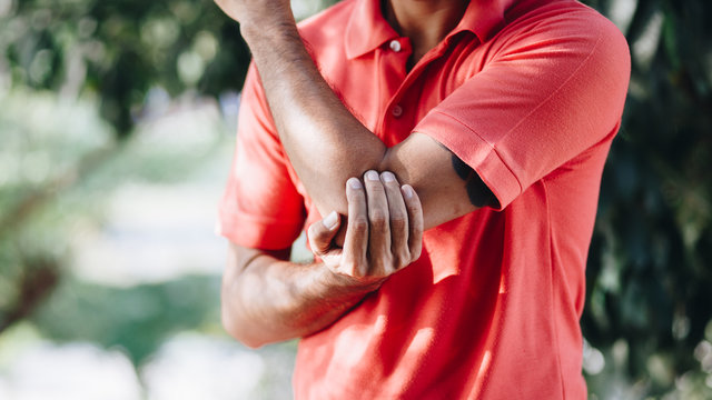 Man suffering from pain in hand or elbow , health care concept