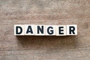 Letter block in word danger on wood background