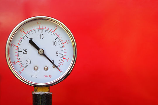 Close up water pressure gauge on red background.