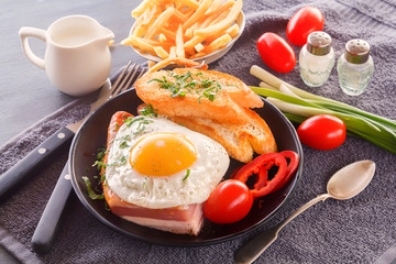 Fried egg with bacon in a black plate with fried pieces of bread, greens tomatoes, a jug of milk and French fries on a gray wooden table. Close-up