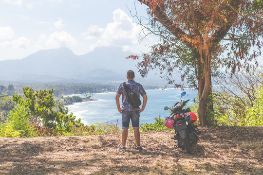 Rare view of a man with scooter on the edge of mountain. Bali island.