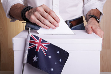 An Australian citizen inserting a ballot into a ballot box. Australia flag in front of it