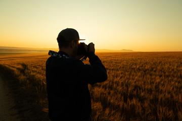 Man take a photo in sunrise in field