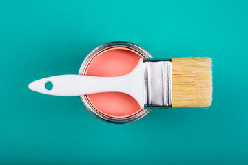 Brush on open can of Living Coral paint on blue pastel background