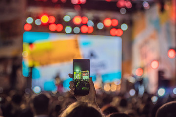 Use advanced mobile recording, fun concerts and beautiful lighting, Candid image of crowd at rock concert, Close up of recording video with smartphone, Enjoy the use of mobile photography