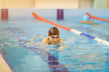 Young woman in goggles and cap swimming breaststroke stroke style in the blue water indoor race pool