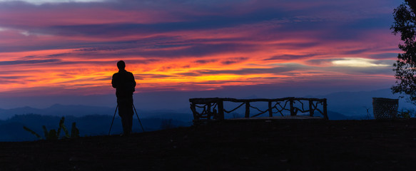 Silhouette of photographer take photos at morning sunrise on peak of mountain