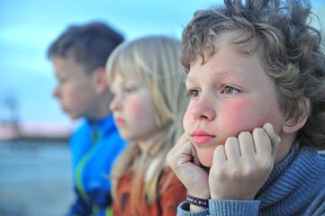 Portrait of three sad boys outdoors