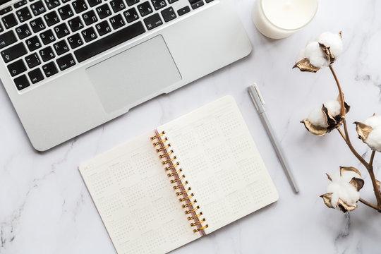 Desktop flatlay items. Laptop, candle, calendar, pen, cotton flower
