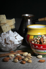 A mug of coffee and different oriental sweets: turkish delight, halva, almond and pistachio