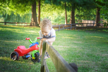 smiling blond curly child playing with bike
