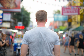 Rear view of young tourist man against view of Khao San road in Bangkok