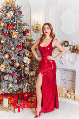 Winter holidays, celebration and people concept - young sexy woman in elegant red dress over christmas interior background