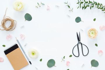 Festive spring composotion with flowers, notebook, gifts, scissors, ribbons, leaves on a white background, top view and flat lay, floral frame