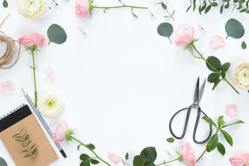 Flat lay of Beautiful green branches and pink white flowers frame on pastel background. Top view. Lifestyle spting composition.