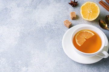 Cup of tea with lemon and brown sugar, cinnamon and anise on the table.