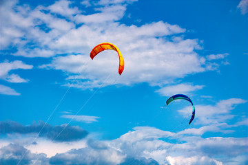 Two kites against a blue cloudy sky