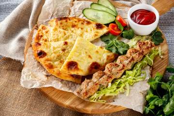Traditional georgian food - shish kebab and khachapuri pie served with fresh vegetables at wooden tray board on table with sack cloth background.