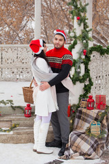 Beautiful young couple of lovers on a walk in the winter in anticipation of Christmas. Christmas decoration gazebo for a date