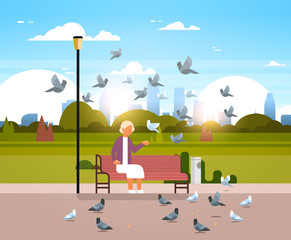 senior woman feeding flock of pigeon sitting wooden bench urban city park cityscape background horizontal flat