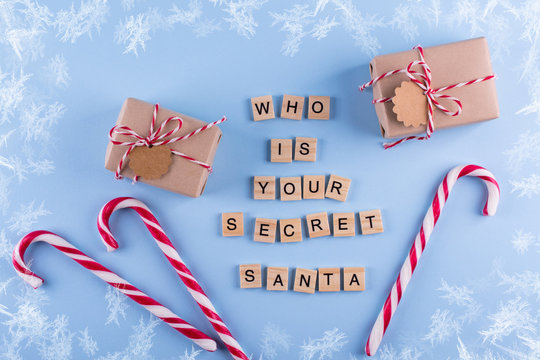 Secret Santa christmas game. Wrapped gift boxes with notes candy cane on blue pastel background top view copyspace. Text from letters Who is your Secret Santa