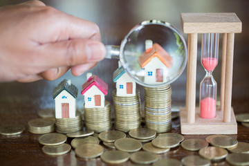 Stack coin and bar graph with grow,  Hand hold a magnifying glass searching for a new home, Loan for real estate or save money for buy a house to family in the future concept.